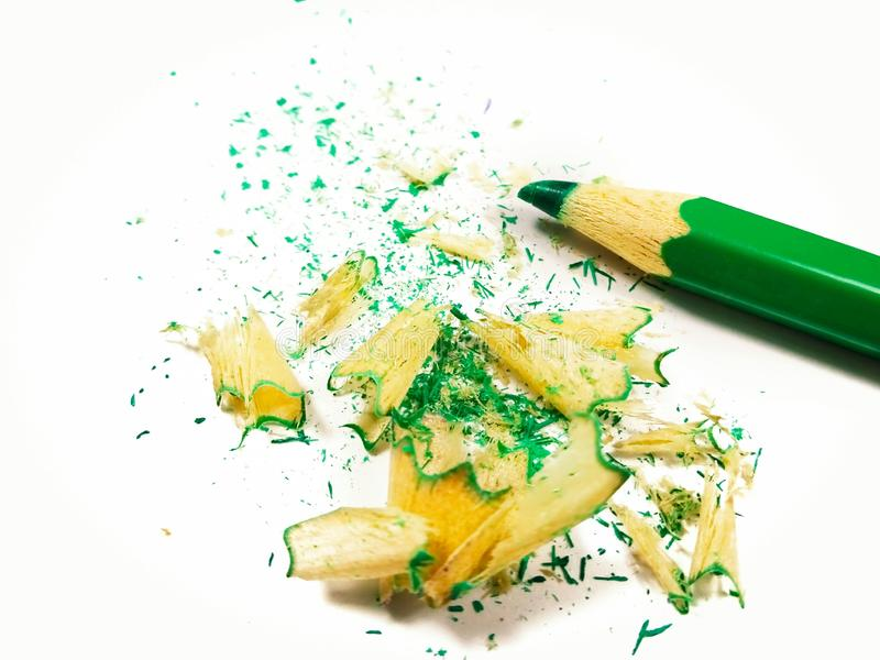 Green crayon pencil with shavings on white background. royalty free stock photography