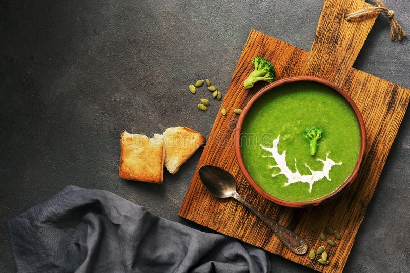 Green cream broccoli soup with sour cream and pumpkin seeds in a ceramic bowl on a cutting board, dark rustic background. stock photos