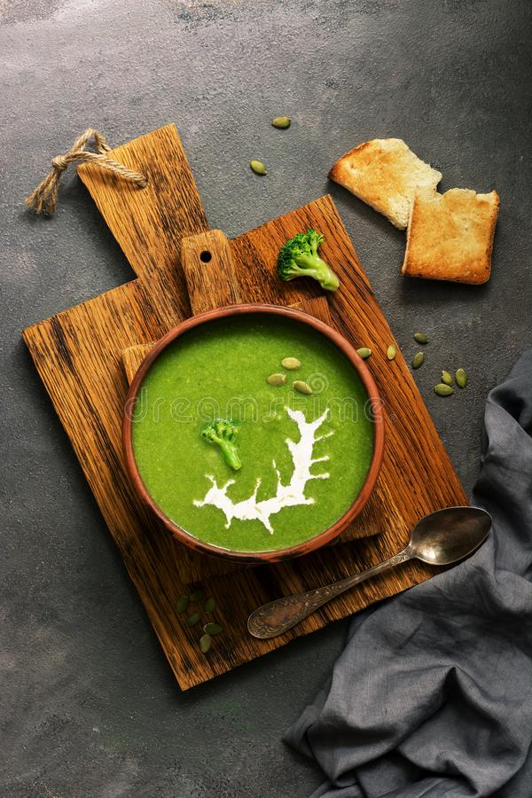 Green cream broccoli soup with sour cream and pumpkin seeds in a ceramic bowl on a cutting board, dark rustic background. View stock photography