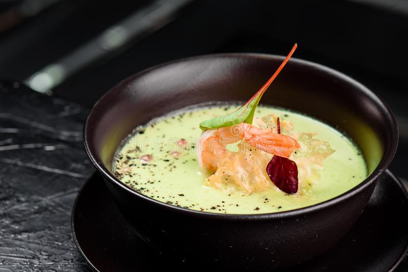 Green Cream Soup with Shrimp . Thai food Shrimp green curry in a dark plate on a black background stock image