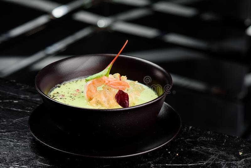 Green Cream Soup with Shrimp . Thai food Shrimp green curry in a dark plate on a black background. Close up royalty free stock photography