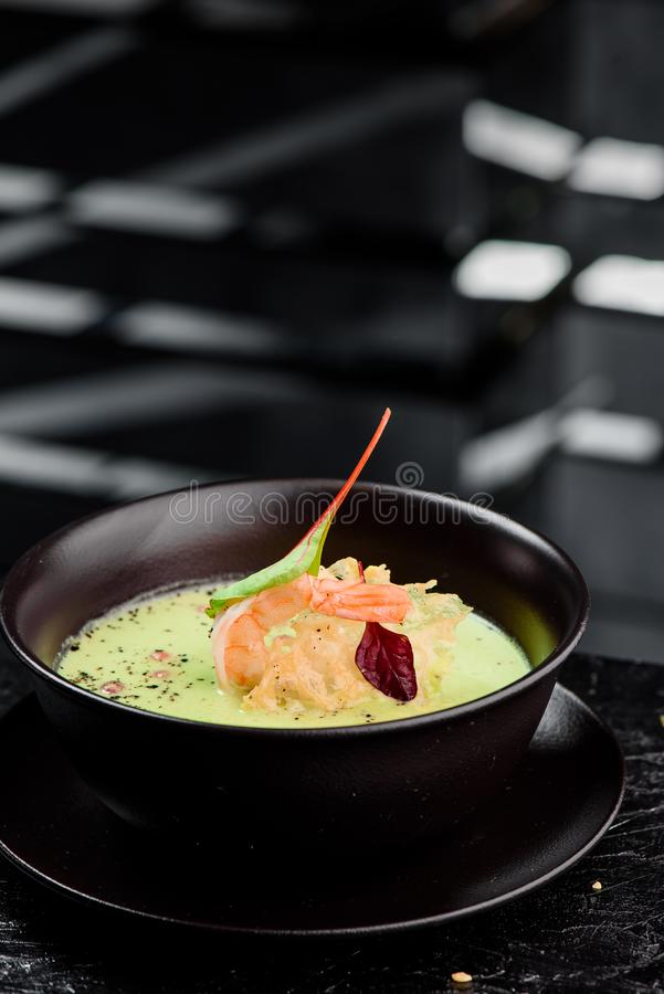 Green Cream Soup with Shrimp . Thai food Shrimp green curry in a dark plate on a black background. Close up stock photography