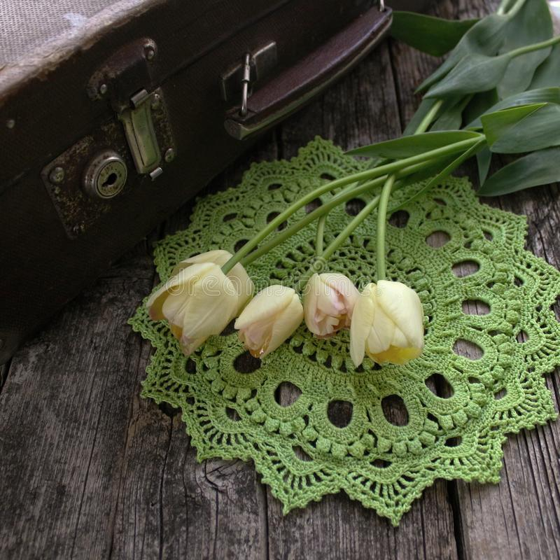 Green crocheted napkin, tulips. Retro and vintage style. The concept of spring, Easter, the sun stock photos