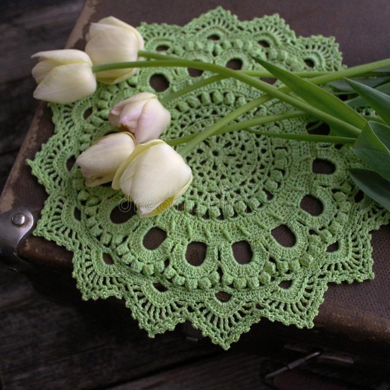 Green crocheted napkin, tulips. Retro and vintage style. The concept of spring, Easter, the sun royalty free stock image