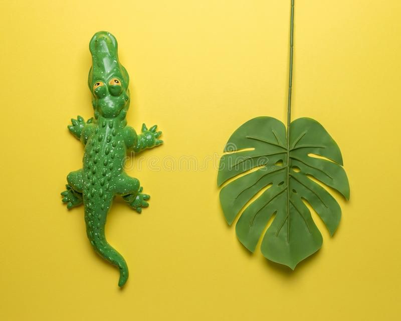 Green crocodile toy with palm leaf on bright yellow background. Minimal art concept stock image