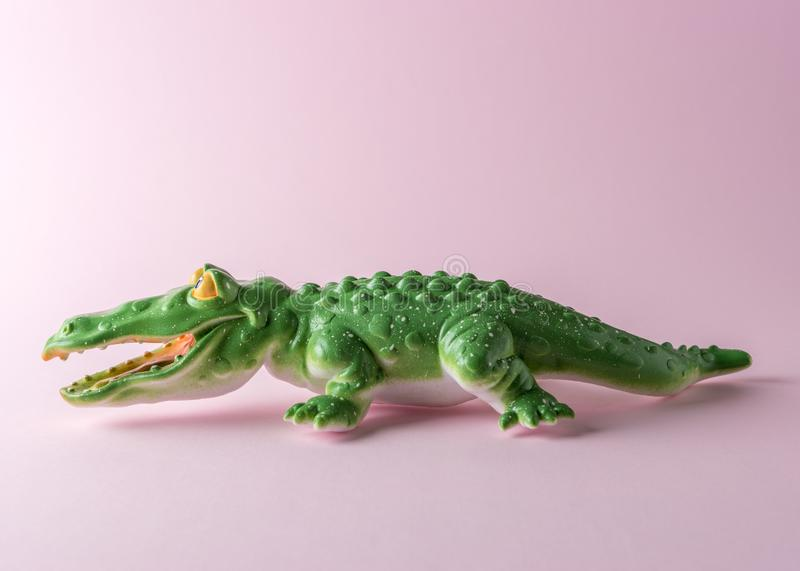 Green crocodile toy on pastel pink background. Minimal art concept royalty free stock photos