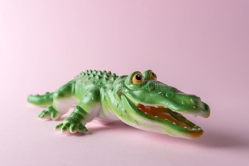 Green crocodile toy on pastel pink background. Minimal art concept royalty free stock photography