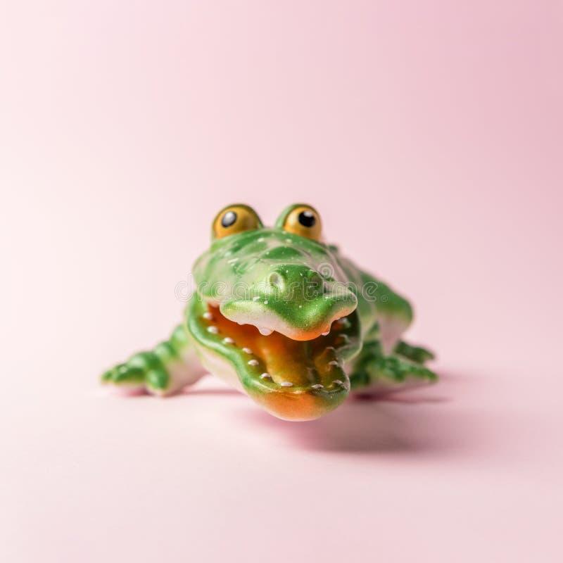 Green crocodile toy on pastel pink background. Minimal art concept stock photos