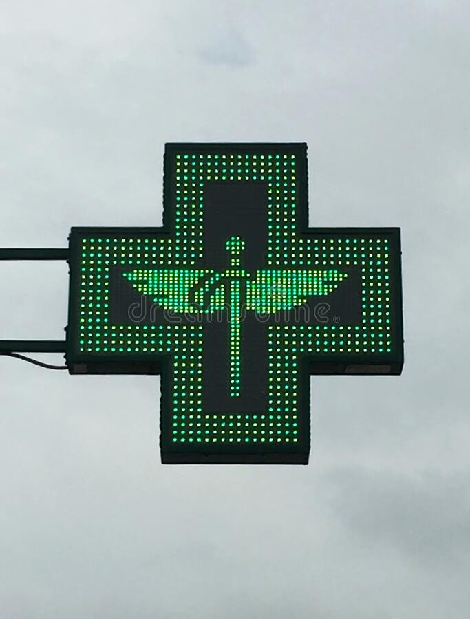 Green cross pharmacy store sign with caduceus. Pharmacy sign. royalty free stock photography