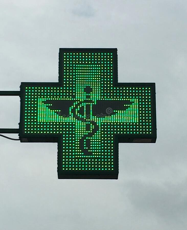 Green cross pharmacy store sign with caduceus. Pharmacy sign. stock image