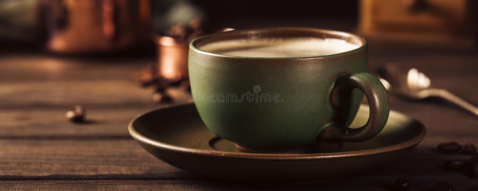 Green cup of coffee with coffee grinder stock images