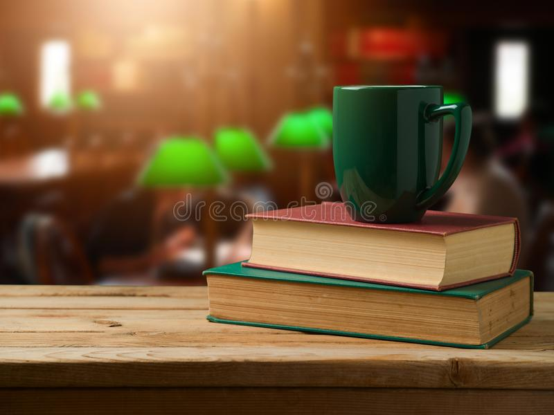Green cup of coffee on stack of books royalty free stock images