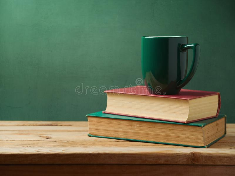 Green cup of coffee on stack of books stock image