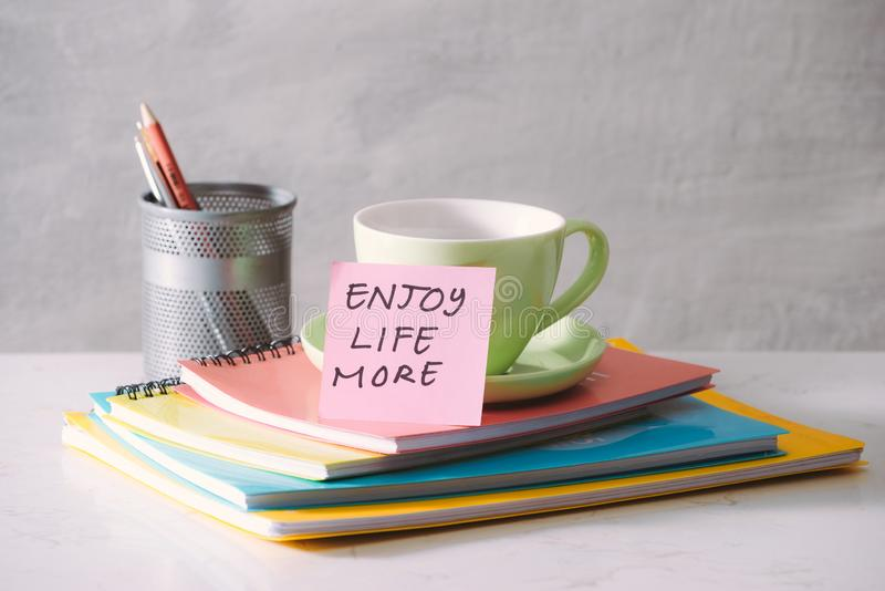 Green cup, notebooks and sticker with text - enjoy life more on light background. Toned business concept with copy space.  stock image