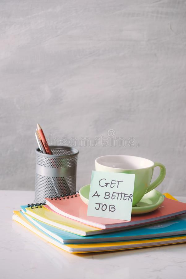 Green cup, notebooks and sticker with text - get a better job on light background. Toned business concept with copy space.  stock photo