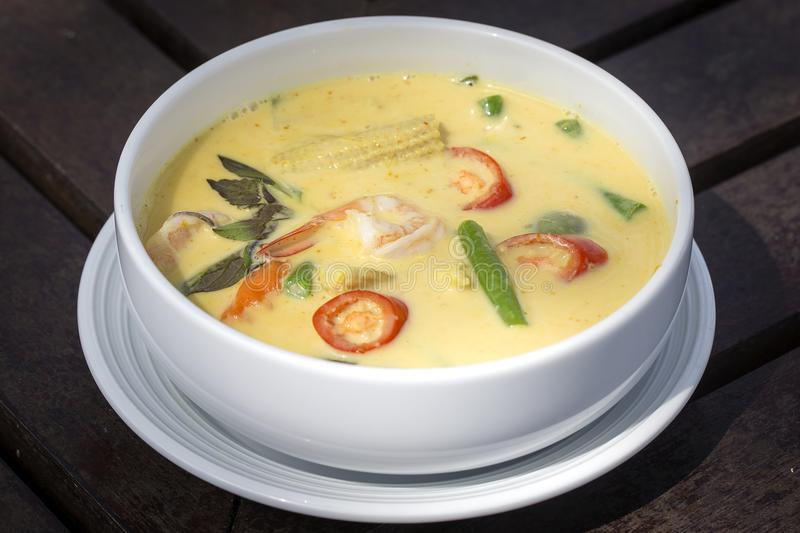 Green curry creamy soup with coconut milk, shrimp, red pepper, bean in white bowl, Thai cuisine stock images