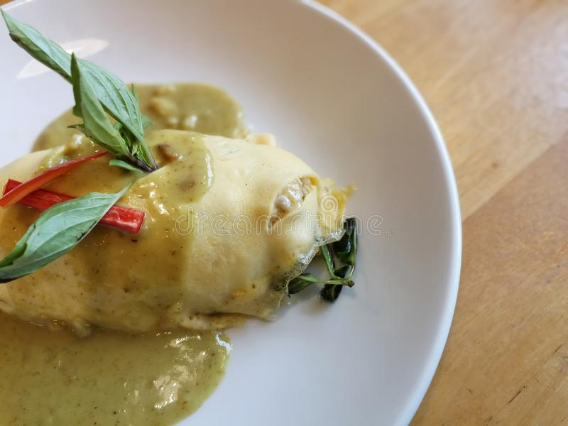 Green curry sauce Omurice with grilled chicken & eggplant - Omelette royalty free stock image