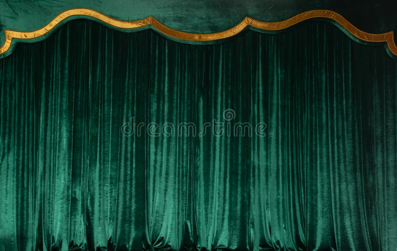 Green curtain of luxurious velvet on the theater stage. Copy space. The concept of music and theatrical art. stock images