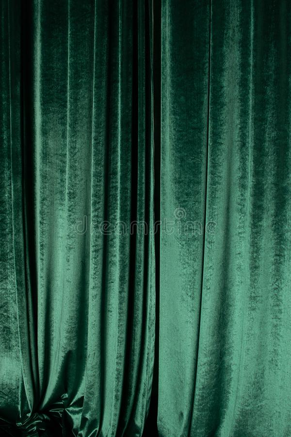 Green curtain of luxurious velvet on the theater stage. Copy space. The concept of music and theatrical art. stock photos