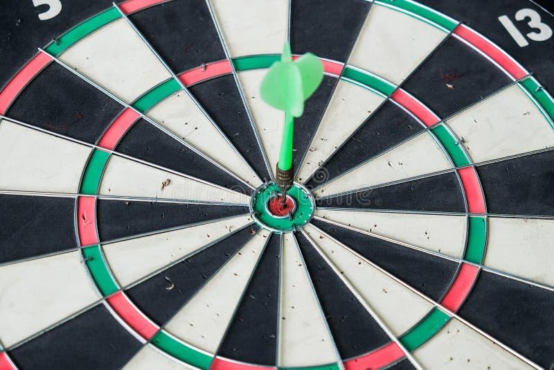 Green dart arrow hitting in the target center. Of dartboard stock image