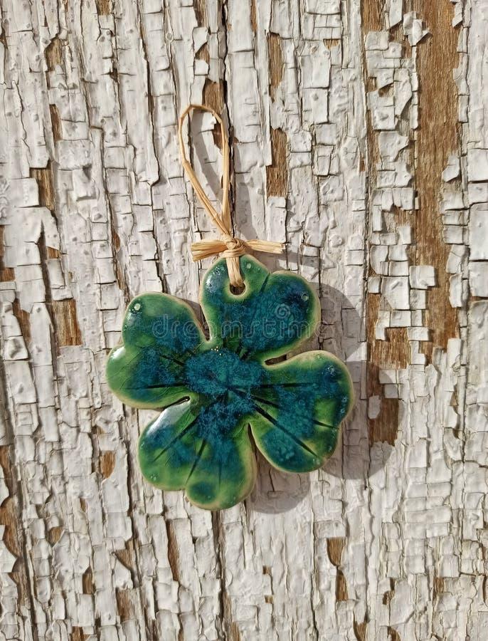 Green decorative four leaf clover on rusty peeling wood surface. Good luck, souvenir. Green decorative four leaf clover on rusty peeling wood surface. Good luck stock photo