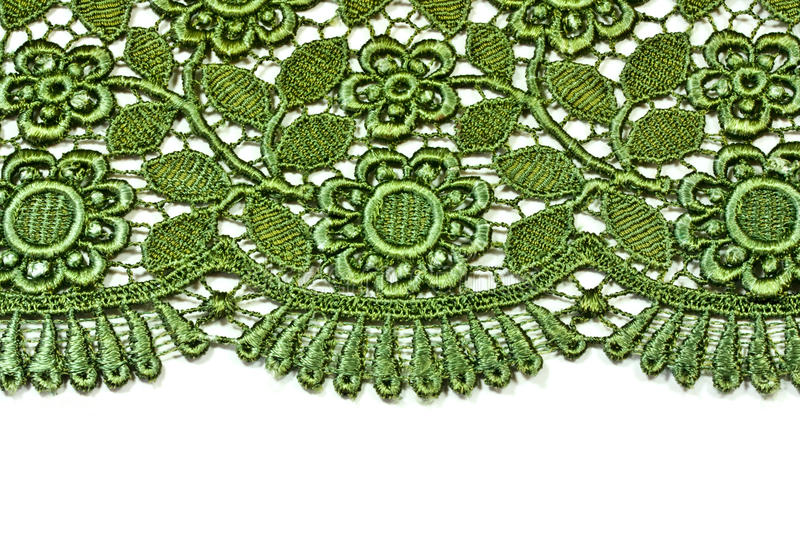 Decorative lace. Close-up of flowers and leaves on the scalloped edge of a piece of lace royalty free stock photography