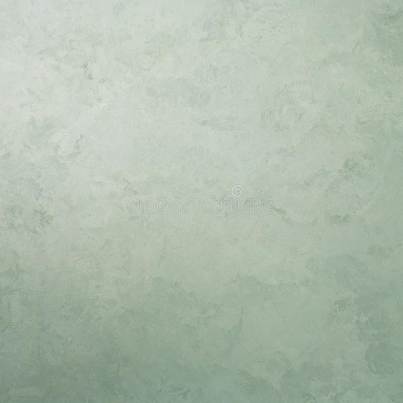 Green decorative plaster texture with pearl glow. Square composition stock photography
