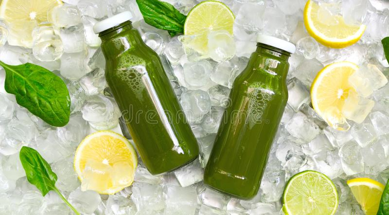 Green Detox drink in glass bottle with fresh lemons and mint royalty free stock photography