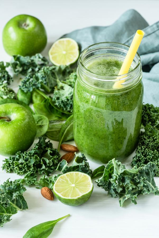 Green detox smoothie or blended juice in glass bottle on white stock photography