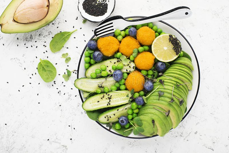 Green different vegetables, avocados, cucumbers, kiwi, blueberries, micro greens, cheese balls, falafel, chickpeas. Top stock images