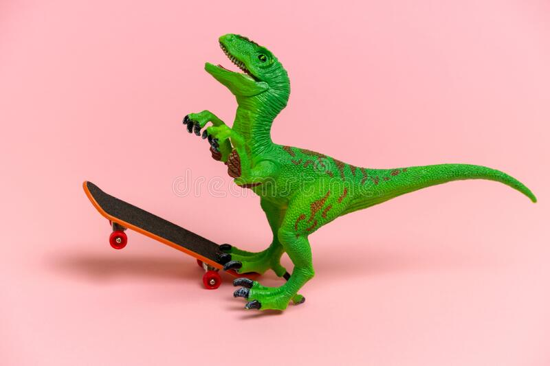 Green dinosaur toy with skate isolated on a pink background. Cute  green dinosaur toy  with skate isolated  on a pink background royalty free stock photography