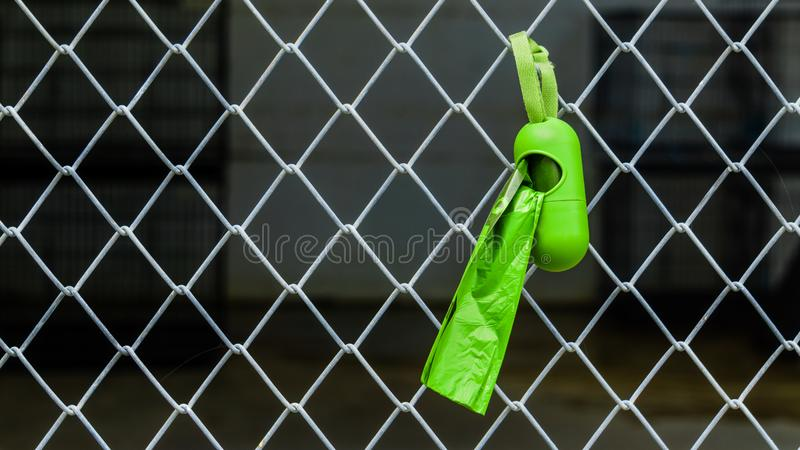 Green dog excrement bags hang on a mesh fence. Cleaning up pets poo in the garden or street with dog poop bags  is an eco-friendly. Solution for pet owners stock image