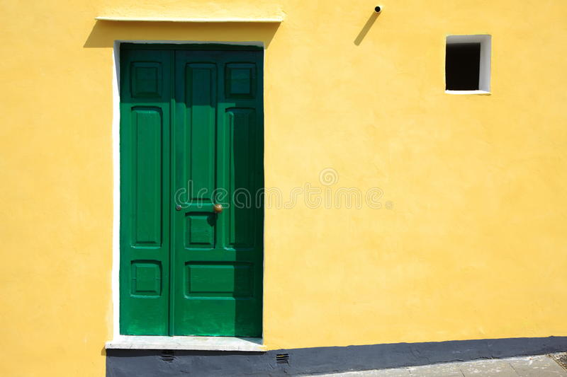 Green door on yellow wall royalty free stock image
