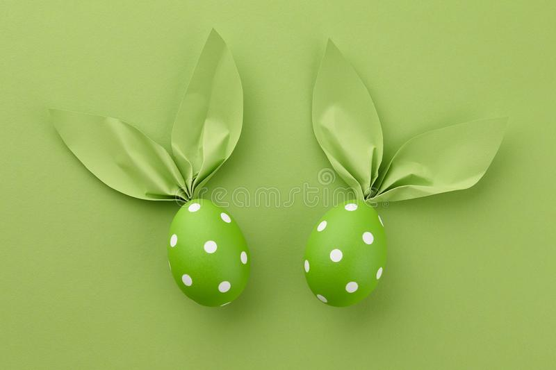 Green dotted Easter eggs with paper bunny ears royalty free stock image