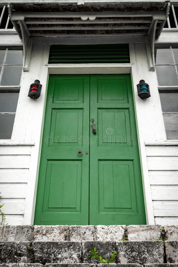 Green double door front entrance at top of stairs/ staircase at a vintage house/home. With vertical sliding glass panel and fixed louver windows to each side stock photos