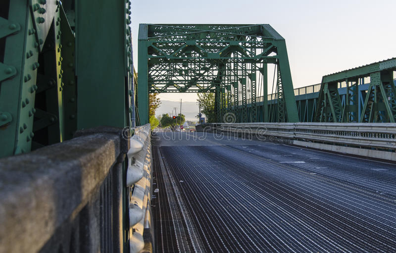 Green Draw Bridge. A view looking down a road across a green structured truss draw bridge royalty free stock images