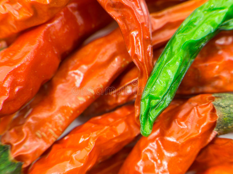 Green dried chilli on other red chillis up close royalty free stock photos