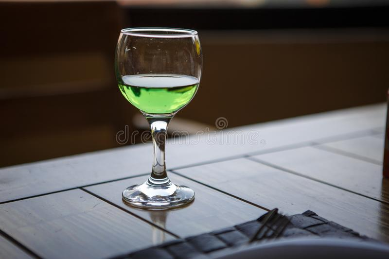 Green drink in the glass is on a wooden table. Mojito, tarragon lemonade, incomplete glass, green lemonade glows in the light royalty free stock photos