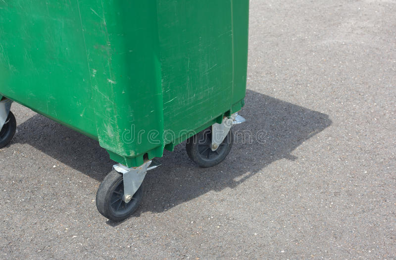 Green dumpster. A green weathered dumpster at the street side. Wheels detail stock photography