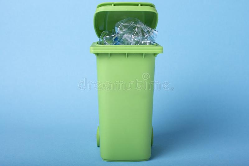 Green dustbin on a blue background with plastic waste. Recycling. Ecological concept stock image