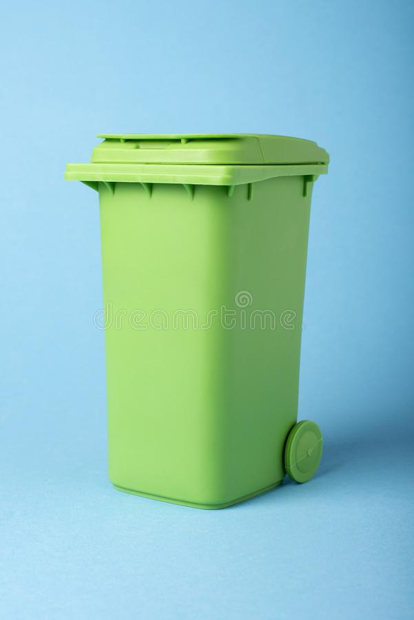Green dustbin on a blue background stock photos