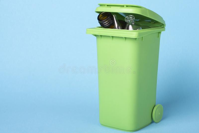 Green dustbin on a blue background with waste glass. Recycling. Ecological concept stock photos