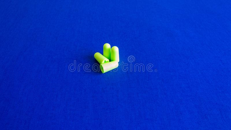 Green earplugs on blue background - image stock photography