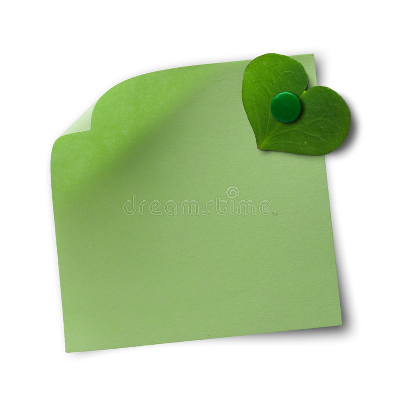 Green and eco friendly memo note. Green memo note over a white background with a clover petal fixed with a thumbtack - concept of ecology or love stock photo