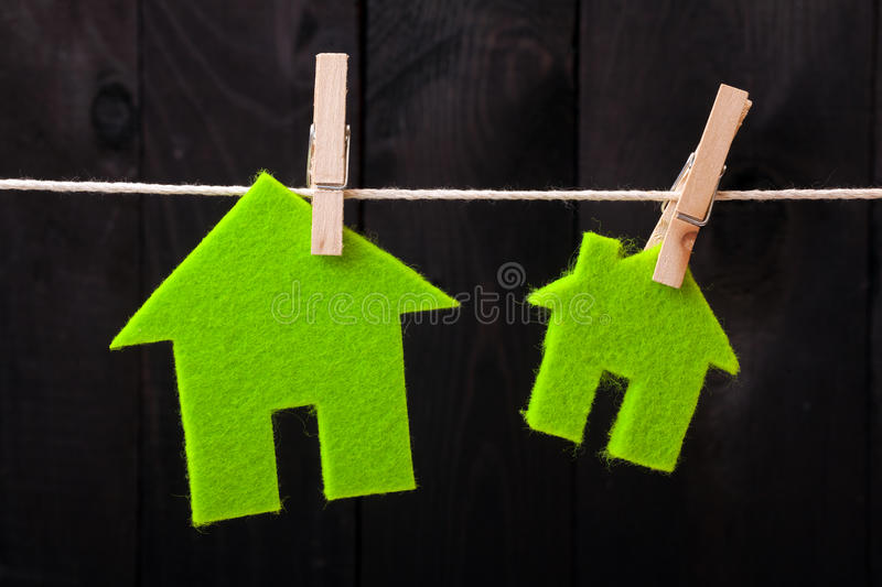 Green eco houses. Attach to rope with clothes pins on dark wooden background royalty free stock image