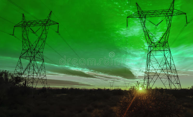 Green Electrical power transmission towers. Over the desert in Arizona at Sunset royalty free stock photography