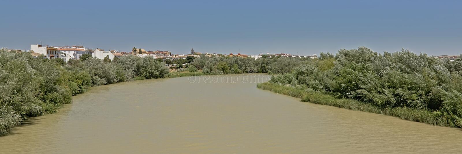 Green borders of Guadalquivir river near Ccordoba. Green embankmnts of Guadalquivir river near Ccordoba, Andalusia, Spain. panoramic view royalty free stock photo