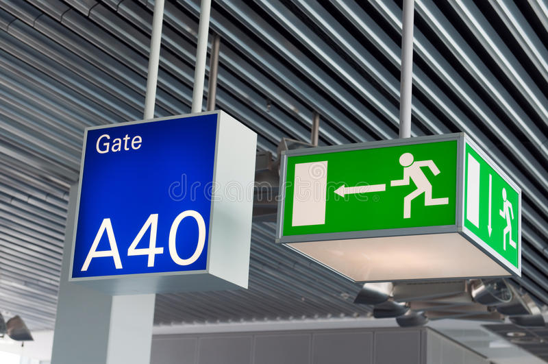 Green emergency exit sign, and blue gate sign royalty free stock images