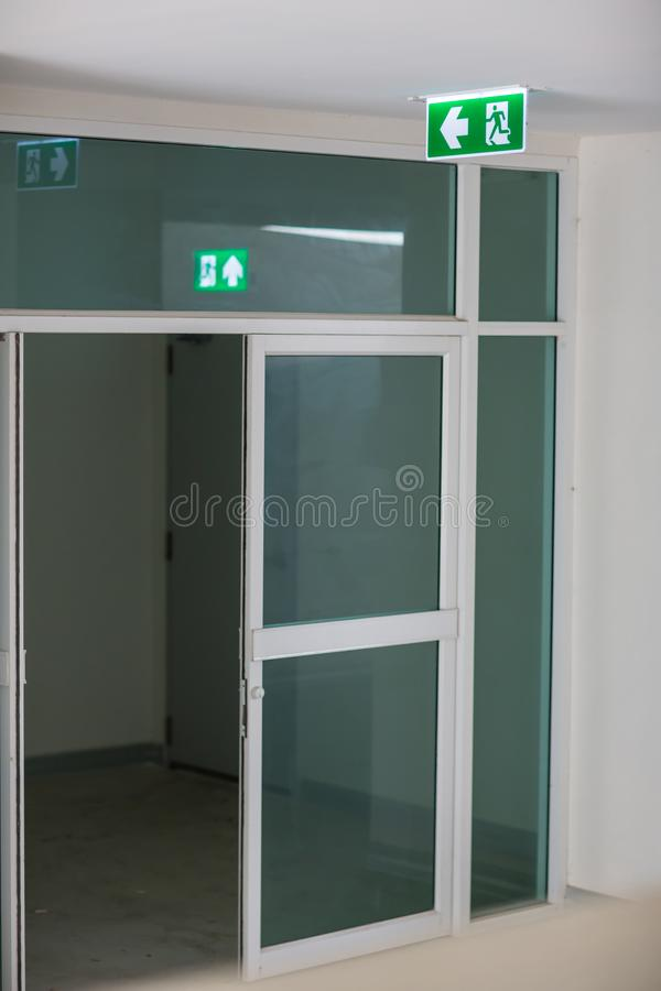 Green emergency exit sign showing the way to escape.Fire exit in the building. royalty free stock image
