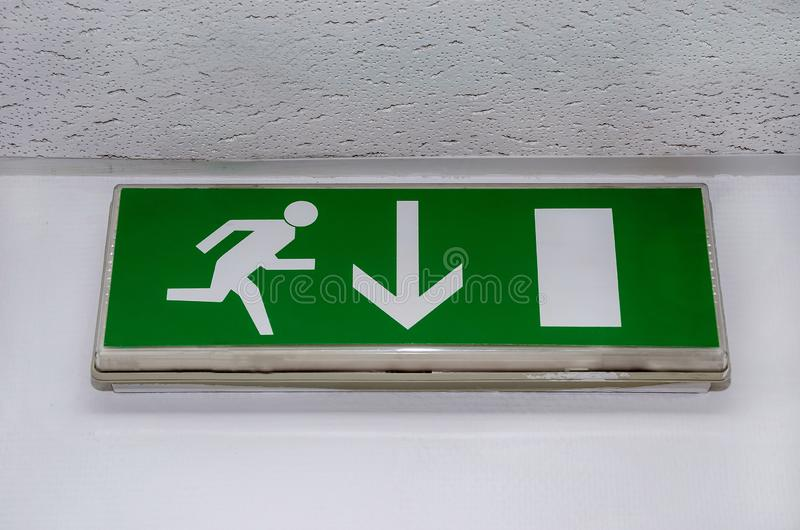 Green emergency exit sign showing the way to escape royalty free stock photography